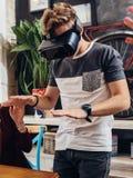 Hombre joven sorprendente que lleva las gafas de la realidad virtual que juegan a un juego interactivo que intenta tocar algo en  Fotos de archivo