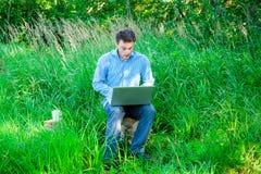 Hombre joven sorprendido al aire libre con una taza y un ordenador portátil Imagen de archivo