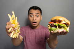 Hombre joven sorprendido con el tamaño de su paquete de porción de la hamburguesa Fotografía de archivo