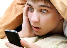 Hombre joven sorprendido con el teléfono Foto de archivo libre de regalías