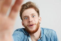 Hombre joven sorprendido con la barba en la camisa de la mezclilla que estira la mano a la cámara sobre el fondo blanco Imagen de archivo
