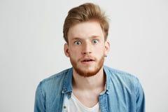 Hombre joven sorprendido con la barba en la camisa de la mezclilla que mira que estira a la cámara sobre el fondo blanco Imagen de archivo