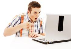 Hombre joven sorprendido con la computadora portátil. El señalar en él. Fotos de archivo