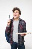 Hombre joven sorprendido con la pluma y el libro Foto de archivo libre de regalías