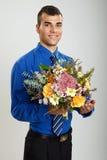 Hombre joven sorprendido con las flores Fotos de archivo