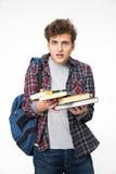 Hombre joven sorprendido con los libros Imágenes de archivo libres de regalías