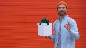 Hombre joven sorprendido del inconformista con el bigote y barba en la sorpresa que sostiene la caja blanca con los regalos en un metrajes