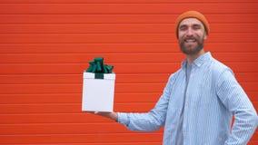 Hombre joven sorprendido del inconformista con el bigote y barba en la sorpresa que sostiene la caja blanca con los regalos en un almacen de video