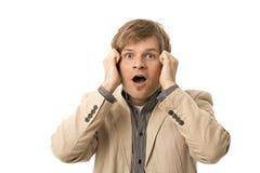 Hombre joven sorprendido que lleva a cabo su cabeza Foto de archivo libre de regalías