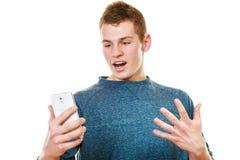Hombre joven sorprendido que mira el teléfono móvil Imagenes de archivo