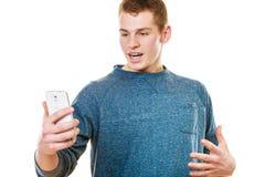 Hombre joven sorprendido que mira el teléfono móvil Fotografía de archivo