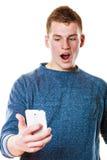 Hombre joven sorprendido que mira el teléfono móvil Fotos de archivo