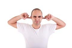 Hombre joven, sosteniendo los dedos en sus oídos Imágenes de archivo libres de regalías