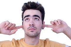 Hombre joven, sosteniendo los dedos en sus oídos, agujereados Foto de archivo libre de regalías