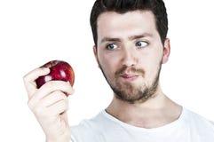 Hombre joven straing en una manzana Foto de archivo libre de regalías