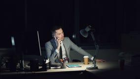 Hombre joven subrayado en el trabajo en oficina tarde en la noche que habla en el teléfono móvil entonces que ríe la sentada del  metrajes
