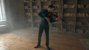 Hombre joven talentoso atractivo que toca el violín sensual El violinista ensaya en el estudio interior contra metrajes