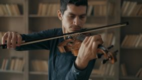 Hombre joven talentoso atractivo que toca el violín sensual El violinista ensaya en el estudio interior contra almacen de metraje de vídeo
