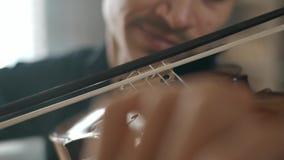 Hombre joven talentoso atractivo que toca el violín sensual El violinista ensaya la cámara lenta del primer 4K almacen de metraje de vídeo
