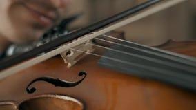 Hombre joven talentoso atractivo que toca el violín sensual El violinista ensaya el primer 4K almacen de video