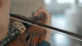Hombre joven talentoso atractivo que toca el violín sensual El violinista ensaya el primer 4K almacen de metraje de vídeo