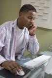 Hombre joven tensado que usa el ordenador Foto de archivo