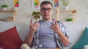 Hombre joven torpe con las agujas que hacen punto MES lento de los vidrios metrajes