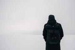 Hombre joven trasero con una mochila negra, viajando en lugares nevados del invierno Imagen de archivo