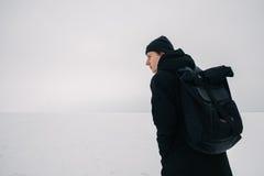 Hombre joven trasero con una mochila negra, viajando en lugares nevados del invierno Fotos de archivo libres de regalías