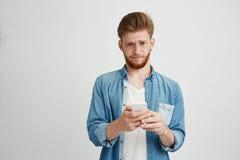Hombre joven trastornado de Dissapointed con la barba que sostiene el teléfono elegante que mira la cámara sobre el fondo blanco Fotografía de archivo