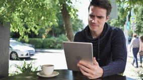 Hombre joven trastornado por la pérdida mientras que trabaja en la tableta metrajes