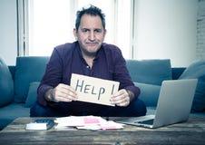Hombre joven trastornado que pide ayuda en problemas de las finanzas del hogar o del negocio de la hipoteca de las cuentas que pa imagen de archivo