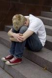 Hombre joven trastornado que se sienta en las escaleras Imágenes de archivo libres de regalías