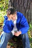 Hombre joven triste con el teléfono Imagenes de archivo