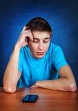 Hombre joven triste con el teléfono Foto de archivo libre de regalías