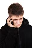 Hombre joven triste con el teléfono móvil Fotos de archivo