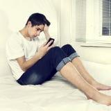 Hombre joven triste con el teléfono móvil Foto de archivo