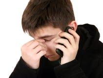 Hombre joven triste con el teléfono móvil Imagen de archivo libre de regalías