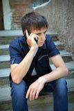 Hombre joven triste con el teléfono móvil Imágenes de archivo libres de regalías