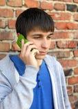 Hombre joven triste con el teléfono móvil Imagen de archivo