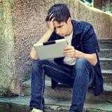 Hombre joven triste con la tableta Fotos de archivo