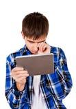 Hombre joven triste con la tableta Imágenes de archivo libres de regalías
