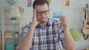 Hombre joven triste con la tarjeta de cr?dito a disposici?n que se sienta en una tabla en un apartamento moderno, concepto la ide almacen de video