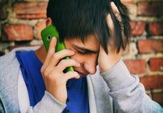 Hombre joven triste con un teléfono Foto de archivo