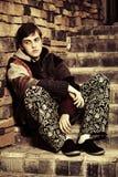 Hombre joven triste del inconformista que se sienta en los pasos Fotografía de archivo libre de regalías