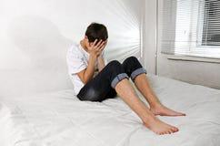 Hombre joven triste en cama Imágenes de archivo libres de regalías