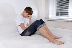 Hombre joven triste en cama Imagenes de archivo