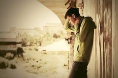 Hombre joven triste en la depresión que se coloca en el puente Foto de archivo