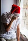 Hombre joven triste en Santa Hat Foto de archivo