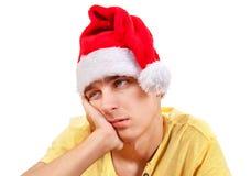 Hombre joven triste en Santa Hat Imagenes de archivo